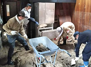 4人でスコップを使い浸入した泥のかき出し作業をしている様子