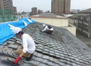 屋根の上で瓦を取り付けている作業風景